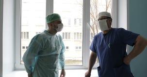 医疗制服和面具的两位年轻医生在医院谈话反对窗口 影视素材