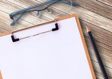 医疗剪贴板和玻璃与铅笔 库存图片