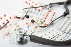 医疗听诊器和不同的药片在白色背景 图库摄影