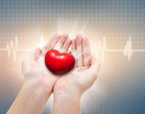 医疗和关心概念,红色心脏在女性手上 免版税库存图片