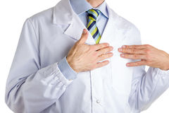 医疗外套的人指向他的心脏的用两只手 免版税库存图片