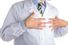 医疗外套的人指向他的心脏的用两只手 库存图片