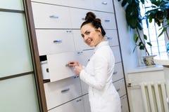 医疗外套立场的妇女接待员 免版税库存图片