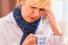 治疗她的流感的资深饮用的茶 免版税库存图片