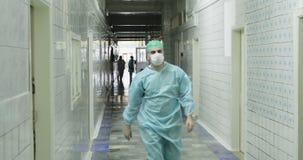 医疗形式和面具的4K A年轻医生在老医院去一个长的走廊 影视素材