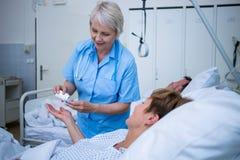 给疗程的护士患者 免版税图库摄影