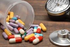 医疗设备和驱散从在木表上的小瓶药片 免版税图库摄影