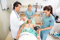 治疗重要患者的医生和护士 库存照片