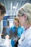 医疗队谈论在X-射线报告在走廊 免版税图库摄影