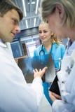 医疗队谈论在X-射线报告在走廊 库存照片