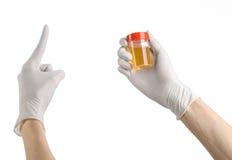 医疗题材:在拿着有对在白色背景的尿的分析的白色手套的医生的手一个透明容器 图库摄影