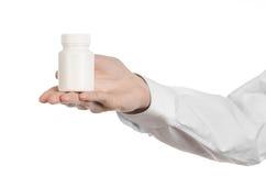 医疗题材:拿着一个白色空的瓶子在白色背景的药片的医生的手 免版税库存照片