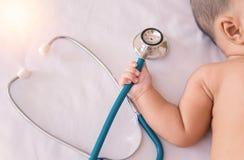 医疗仪器听诊器在手中新出生的女婴 免版税库存照片