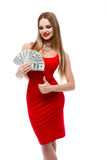 疯狂拿着很多100美金和显示赞许的红色礼服的美丽的少妇所有好 免版税库存照片