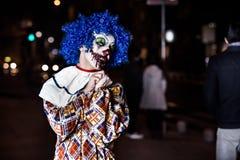 疯狂的丑恶的难看的东西邪恶的小丑在镇在使人的万圣夜冲击和惊吓 免版税库存照片