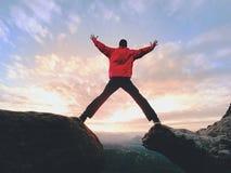 疯狂的人 远足者在岩石峰顶跳 在落矶山脉的美妙的心情, 免版税库存图片
