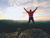 疯狂的人 远足者在岩石峰顶跳 在落矶山脉的美妙的心情, 图库摄影