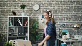 疯狂的企业家跳舞在听到音乐的办公室通过耳机 股票录像
