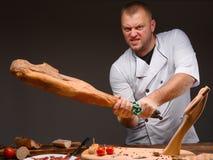疯狂的厨师在有猪肉腿的厨房里在手上 关闭与大型jamon的水平的图象在手上 免版税库存图片