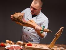 疯狂的厨师在有猪肉腿的厨房里在手上 西班牙jamon 免版税图库摄影