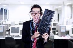 疯狂的商人举行键盘在办公室 库存图片