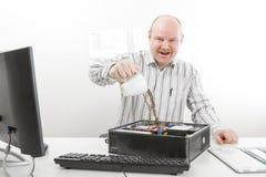 疯狂的在计算机底盘的商人倾吐的咖啡 图库摄影