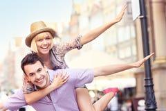 年轻疯狂的夫妇获得乐趣在城市 免版税库存图片