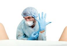 疯狂的妇产科医师审查一名患者 疯狂的医生表示不同的情感和做另外hand& x27; s标志 库存图片