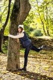 年轻疯狂的妇女在秋天的拥抱树户外 免版税库存照片