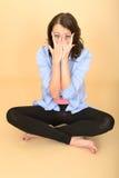 年轻疯狂的妇女坐拉扯傻的表情的地板 免版税库存图片