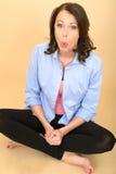 年轻疯狂的妇女坐拉扯傻的表示的地板 免版税库存照片
