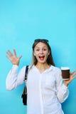疯狂的妇女用在蓝色墙壁附近的杯子咖啡 库存图片