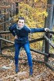 疯狂的少妇在秋天森林里取笑,远足题材 免版税图库摄影