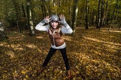 疯狂的少妇在秋天森林里取笑 免版税库存图片
