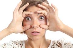 疯狂的少年女孩疲倦了设法张开与手指的眼睛 免版税库存照片