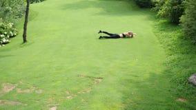 疯狂的懒惰女孩有在草的乐趣辗压在公园 胡闹笑话概念 影视素材