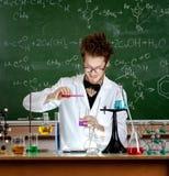 疯狂的教授倾吐在烧杯的若干液体 库存图片