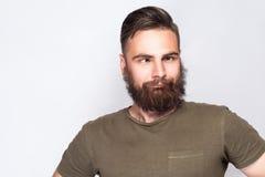 疯狂的斗眼的有胡子的人画象有深绿T恤杉的反对浅灰色的背景 免版税库存照片