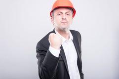 疯狂的显示拳头的工程师佩带的安全帽喜欢战斗 库存图片