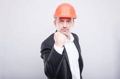 疯狂的显示拳头的承包商佩带的安全帽喜欢战斗 库存图片