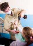 疯狂的牙医对待不幸的患者的牙 患者害怕 库存照片