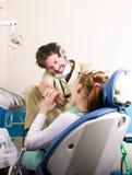 疯狂的牙医对待不幸的患者的牙 患者害怕 免版税库存照片