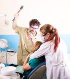 疯狂的牙医对待不幸的患者的牙 患者害怕 图库摄影
