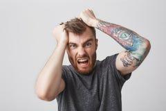 疯狂的美丽的有胡子的人和在偶然灰色衬衣的时髦的发型画象有tattoed胳膊的撕毁头发用手 库存照片