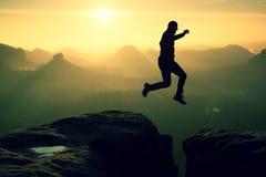 疯狂的远足者跳在峭壁之间 惊人的山,重的薄雾 免版税库存照片