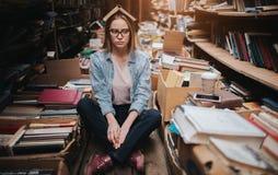 疲乏和哀伤的少年坐在许多书中的地板 也有在她的头的一本被打开的书 这个女孩 库存图片