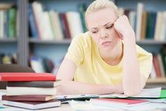 疲乏和沮丧的学生在图书馆里 免版税库存图片