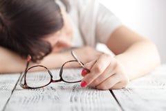 疲乏女实业家睡着在她的有眼睛gl的工作场所 库存照片