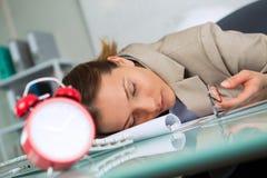 疲乏女实业家睡着在工作场所 免版税图库摄影