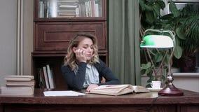 疲乏少妇睡着在书,当坐在桌上时 股票录像